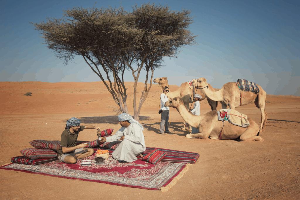 Menschen und Kamele in der Wüste Omans