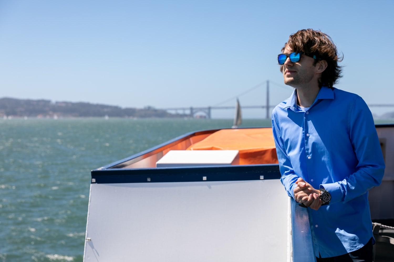 Junger Mann mit Sonnenbrille auf Boot