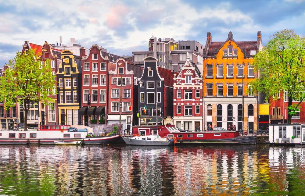 Die alten, bunten Häuser von Amsterdam spiegeln sich im Wasser der Amstel