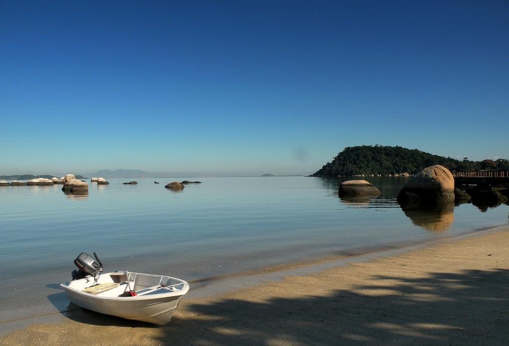 Tropischer Strand mit seichtem Wasser und kleinem Boot.