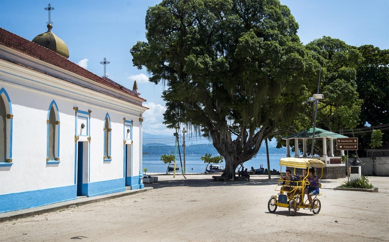 Kleine weiß-blaue Kapelle mit Meerblick und Tuktuk