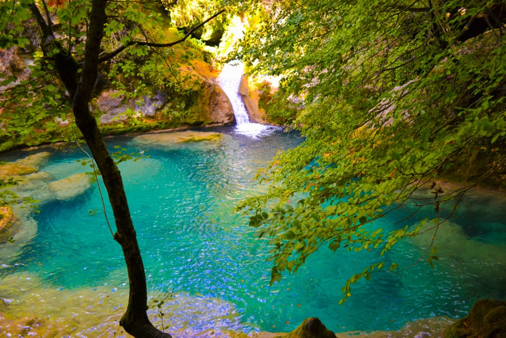 Wasserfal mit kleinem Bergsee mit türkisfarbenem Wasser mitten im Grün des Waldes