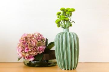zwei verschiedene Vasen, eine mit Holz, eine aus Keramik mit schönen blumen