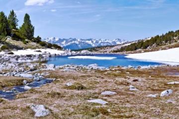 Bergsee mit Resten von Schnee und Panorama