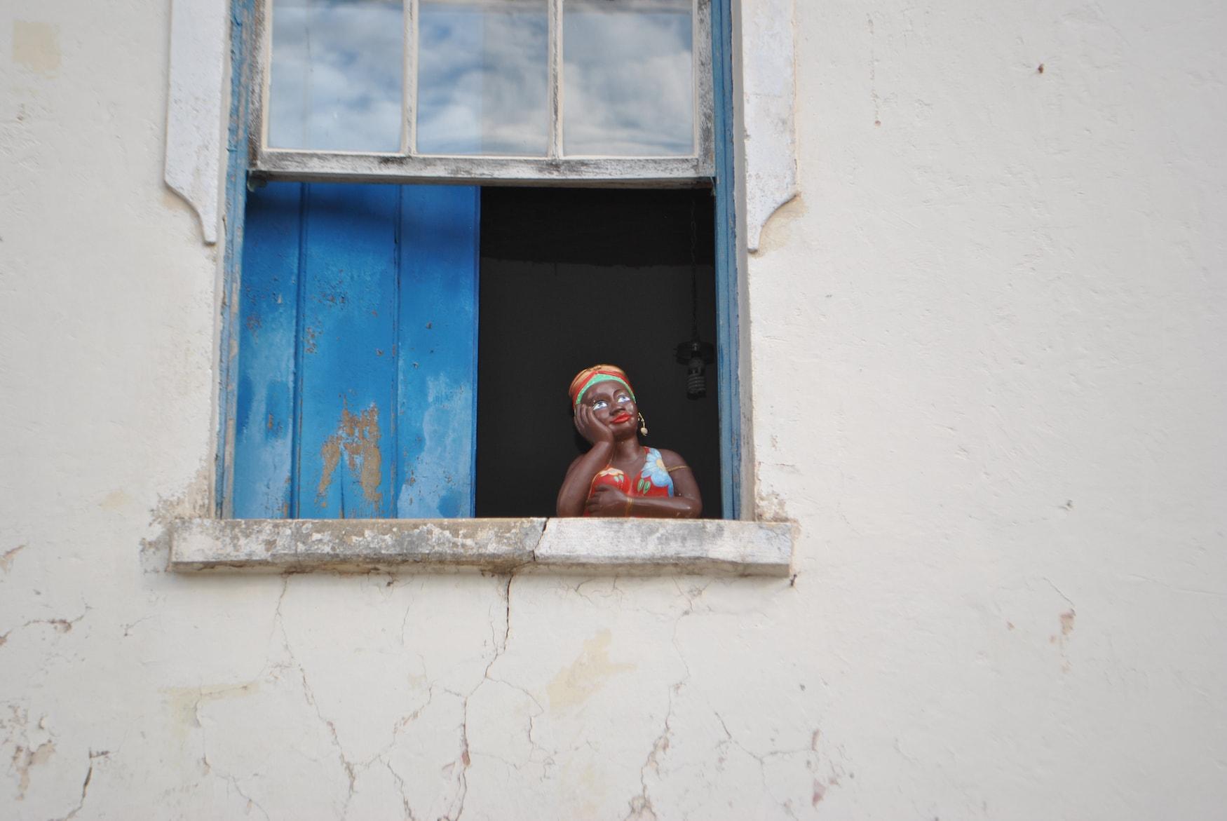 Schwarze Frauenfigur guckt aus Fenster in einem Souvenir-Shop in Salvador in Bahia, Brasilien