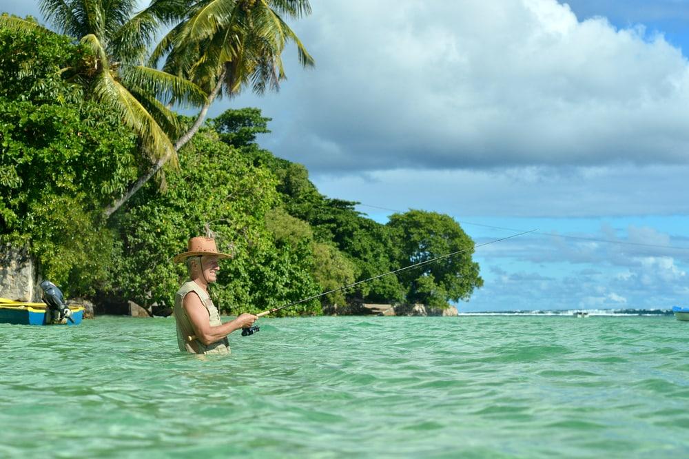 Älterer Mann im Meer beim Angeln