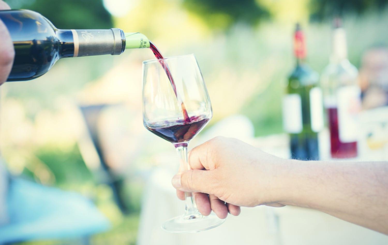 Frauenhand mit Weinglas, dass gerade mit Rotwein gefüllt wird.