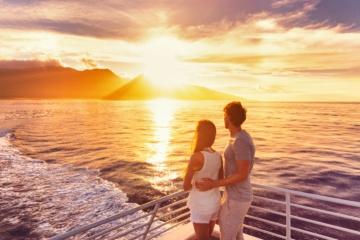 Pärchen auf Kreuzfahrtschiff blickt in Sonnenuntergang