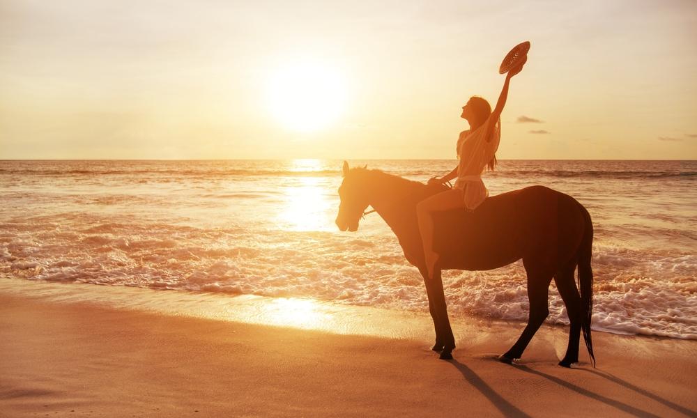 Frau reitet auf Pferd am Strand