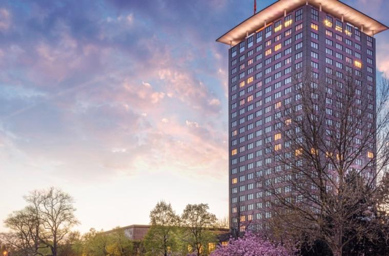 Hohes Hotelgebäude an Kanal im Abendlicht.