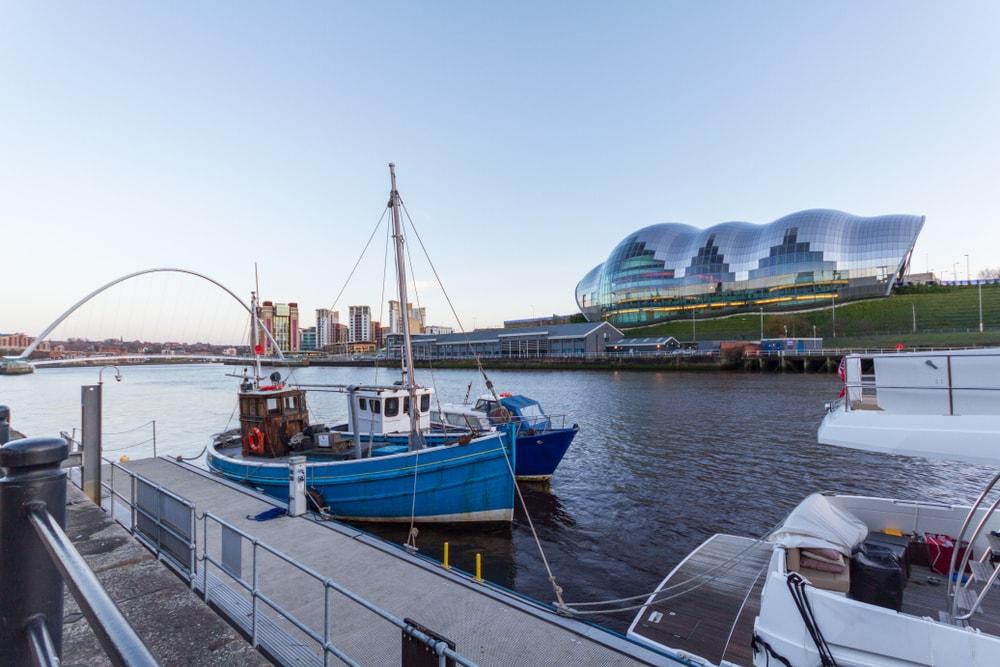 Fluss mit alten Fischerbooten und futuristischem Gebäude,
