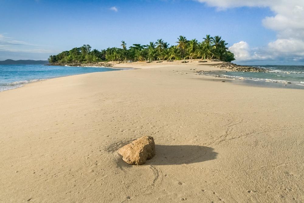 Sandbank zu kleiner tropischen Insel mit Palmen