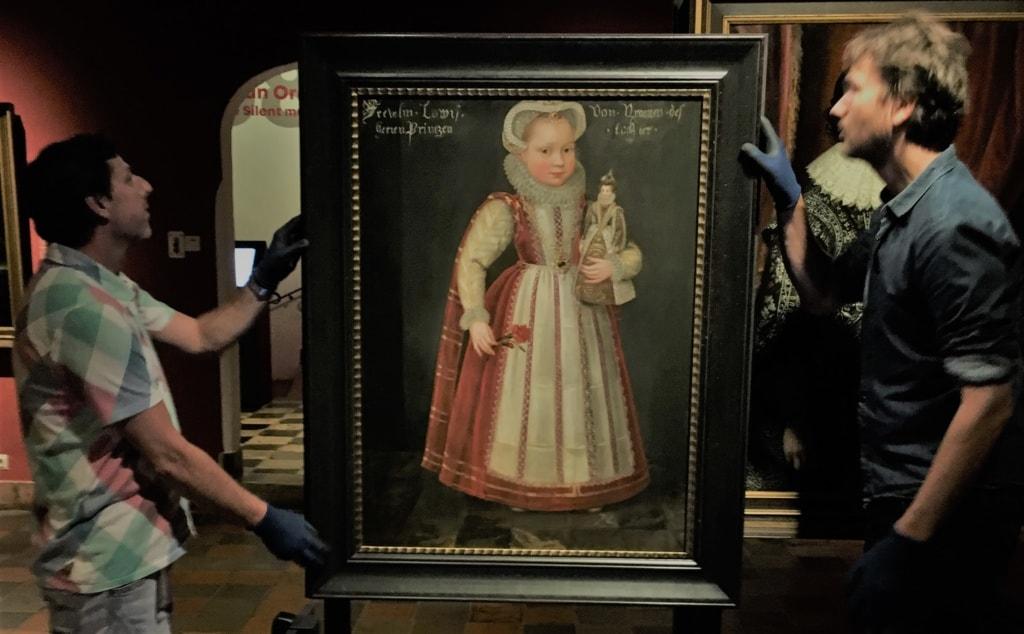 Mitarbeiter des Museums Prinsenhof Delft hängen das Portrait von Louise Juliana auf