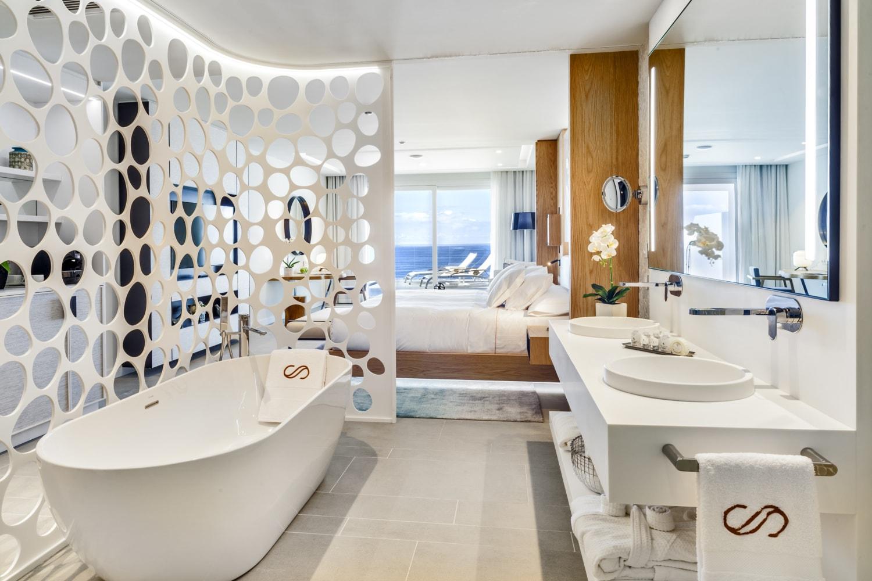 Luxussuite mit großer Badewanne und Blick aufs Meer.