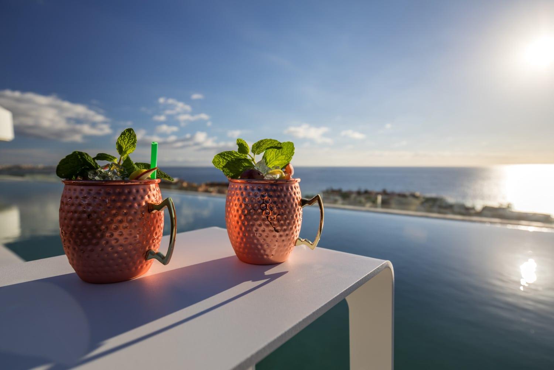 Zwei Cocktails vor Pool mit Meerblick.