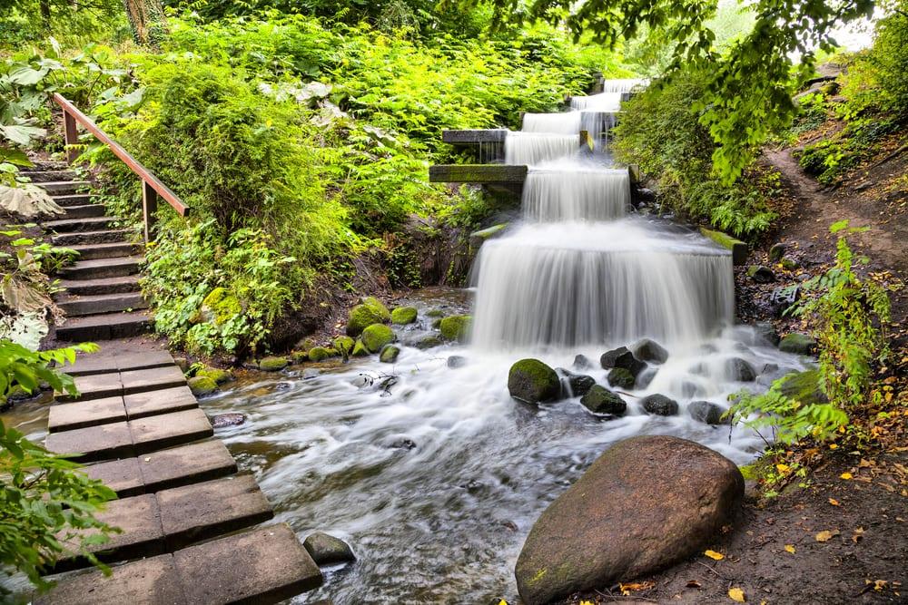 Angelegter Wasserfall in Park mit Geünhängen