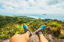 Wanderer mit ausgestreckten Beinen auf Plateau blickt auf die Küste der Seychellen