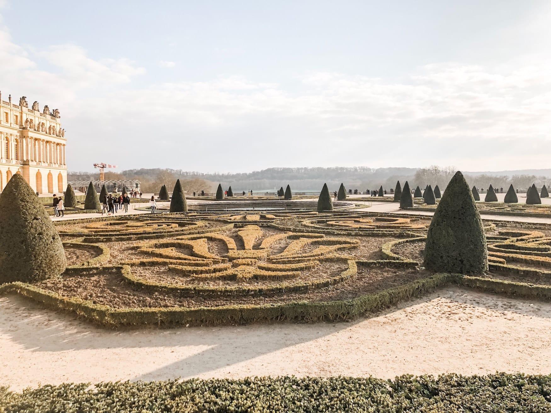 Menschen spazieren durch den Schlosspark von Versailles an einem Herbsttag
