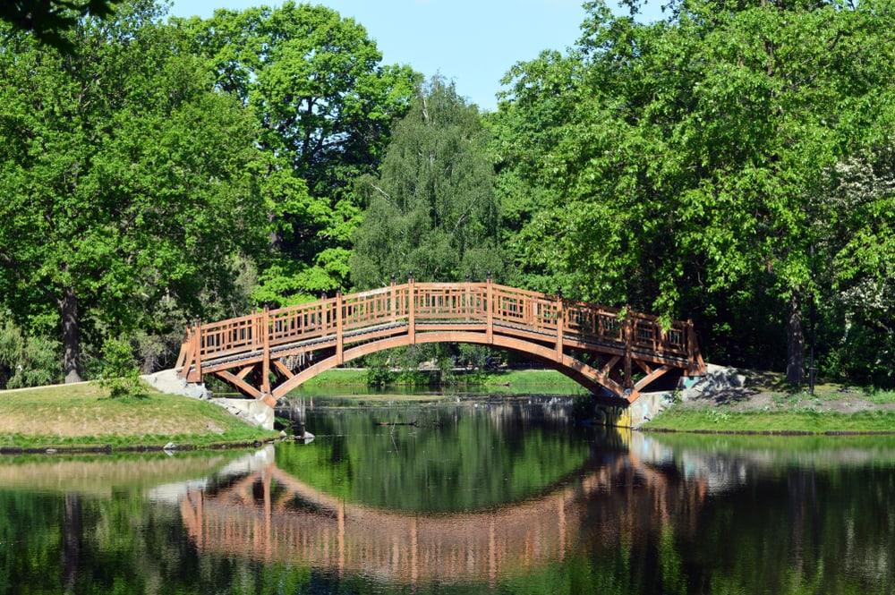Romantische Brücke in grünem Park spiegelt sich in See.