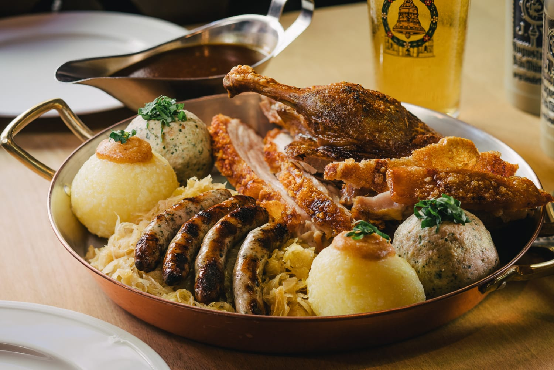 Teller mit Nürnburger Bratwürste, Sauerkraut und Klößen in uriger Atmosphäre.