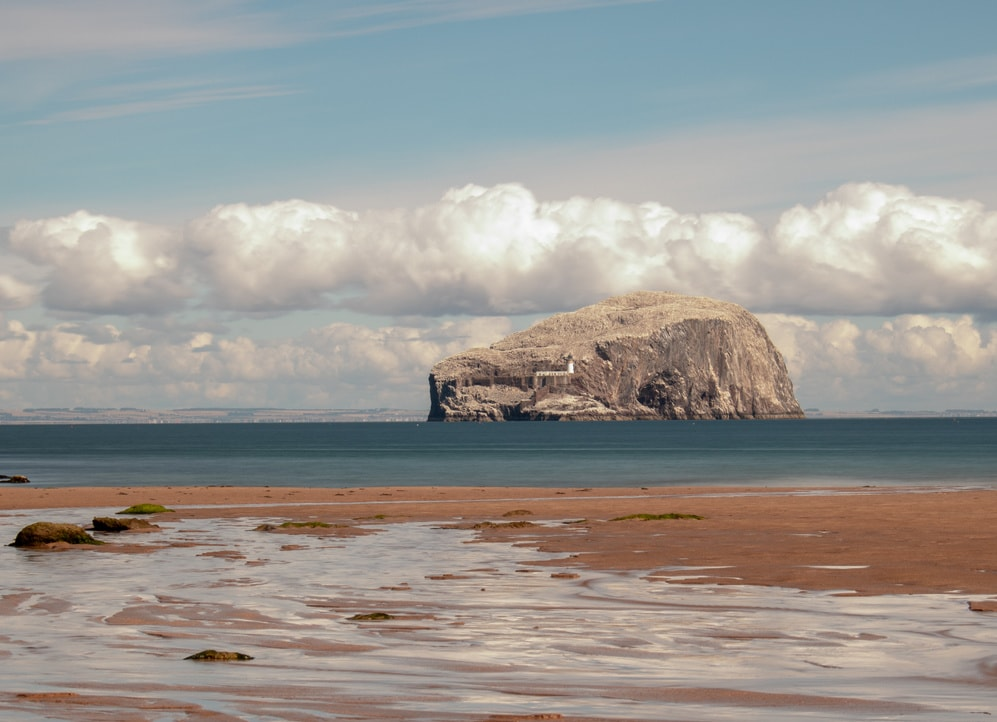 Wilder rötlicher Strand vor Meer mi Felsinsel