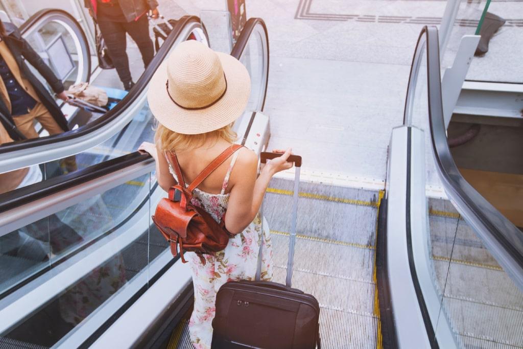 Frau mit Gepäck auf einer Rolltreppe im Flughafen