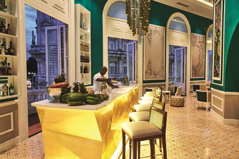 Edelbar mit Dunkelgrünen Wänden und goldener Bar.