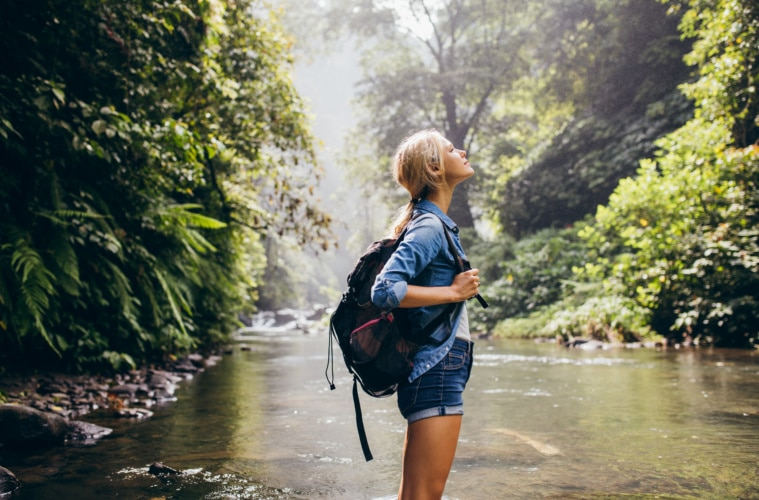 Side view shot relaxed young woman with backpack standing by the stream.