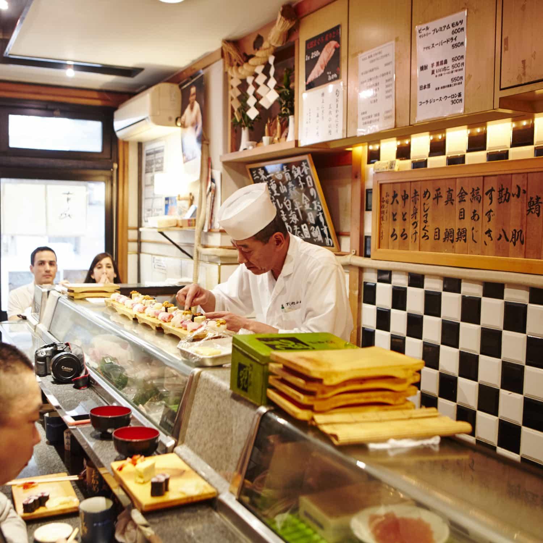 Mann bereitet Sushi in einem japanischen Restaurant zu