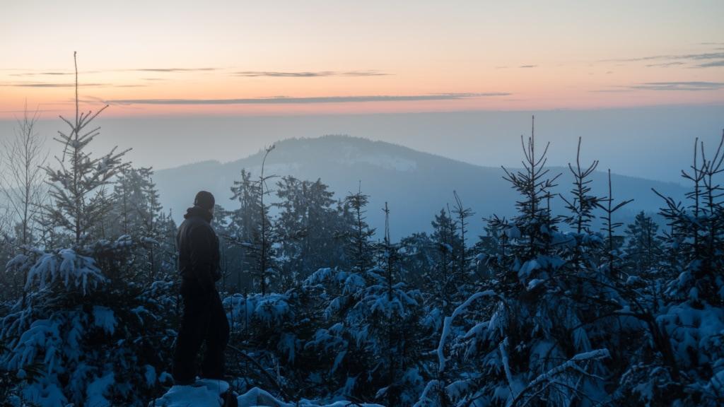 Mann blickt auf Winterlandschaft