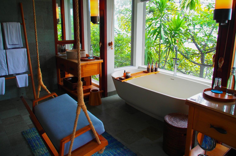 Luxusbadezimmer mit Badewanne mit Blick in die Tropen und Schaukel in Bad