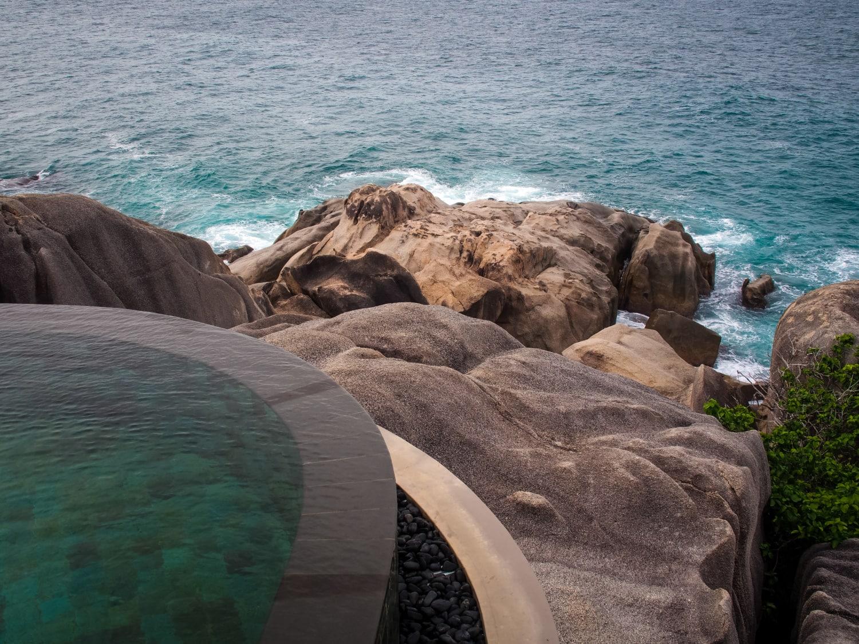 Infinity-Pool mit Blick auf schroffe Felsen und Meer