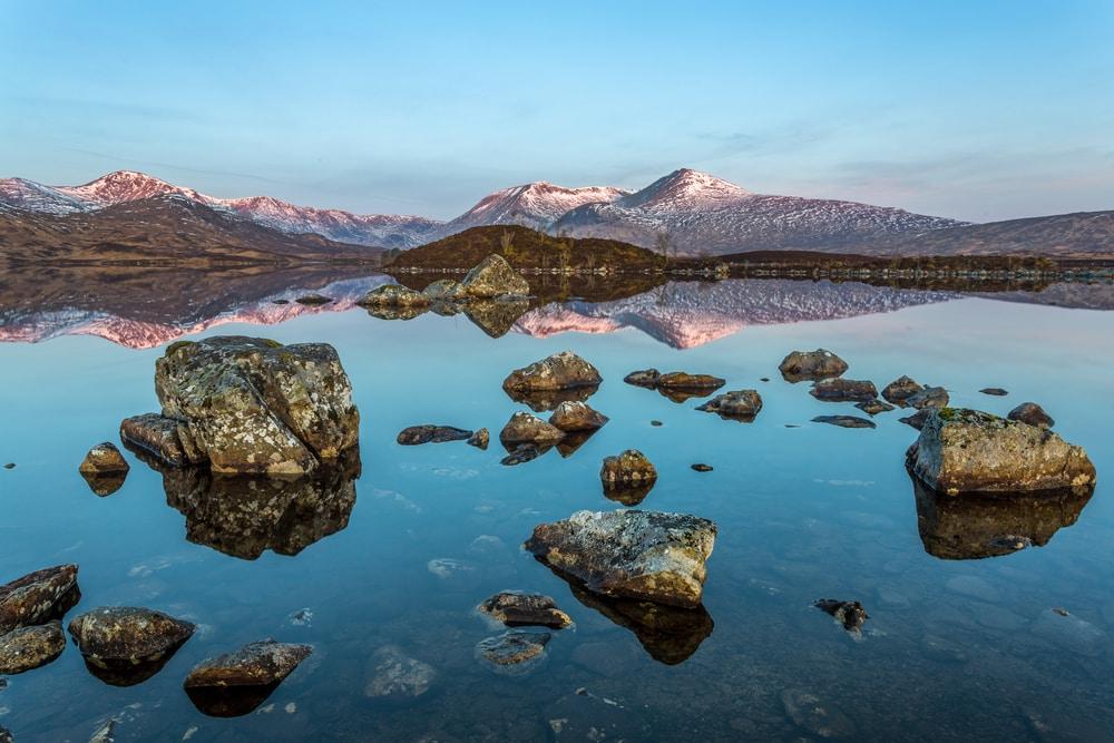 Seenplatte in Abenddämmerung mit Felsen und Spiegelung in karger Landschaft