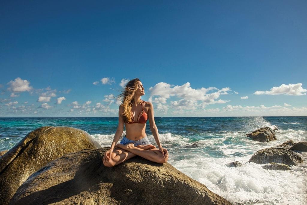 Frau praktiziert Yoga auf einer Klippe auf Aruba
