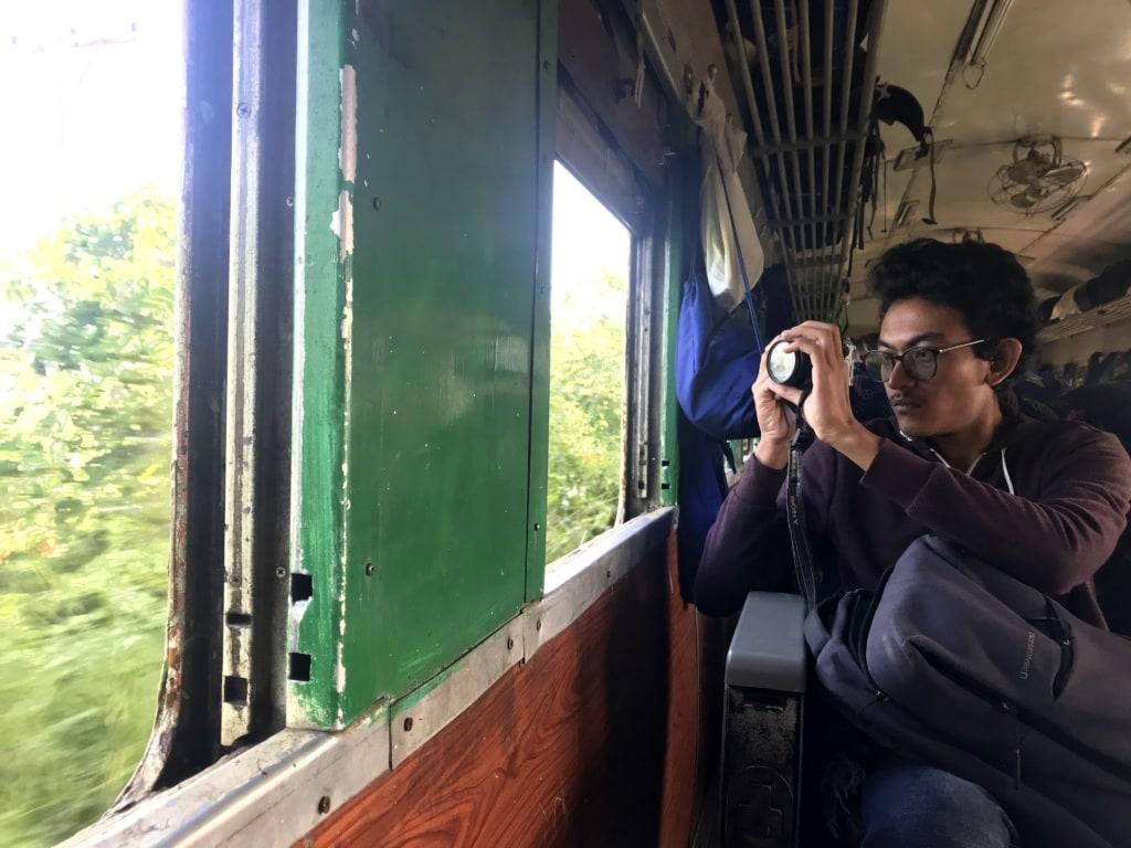 Tourist sitzt im Zug am Fenster und macht ein Foto mit seiner Kamera