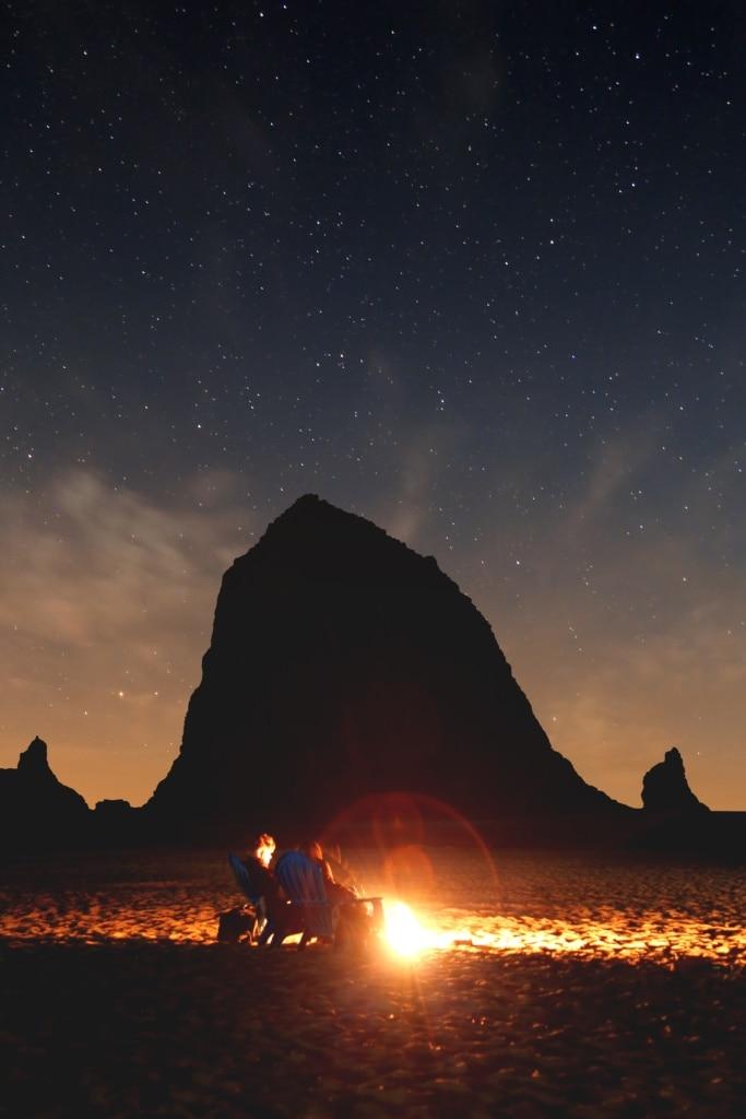 Paar bei Sonnenuntergang mit Feuerstelle am Strand