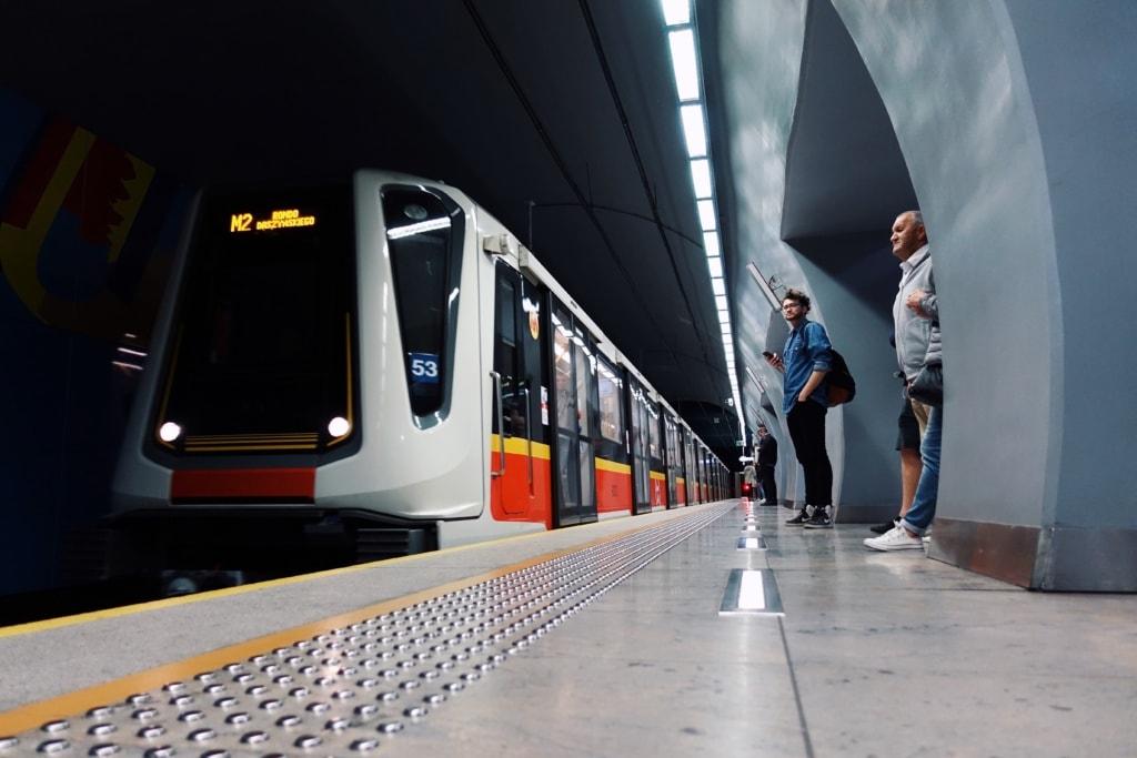 U-Bahn am Gleis und wartende Passagiere in der Metro Warschau