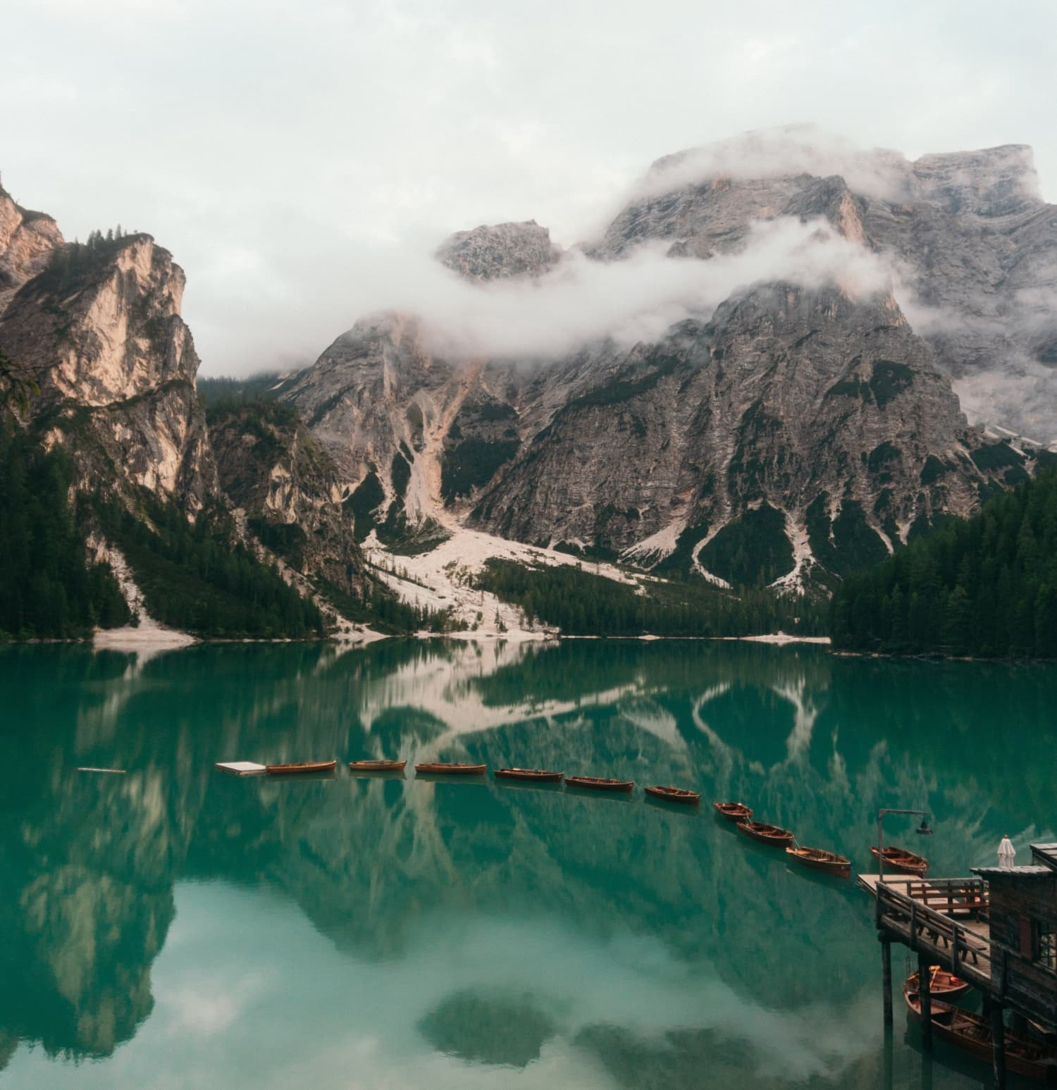 Türkiser Bergsee mit alten Booten und Wolken.