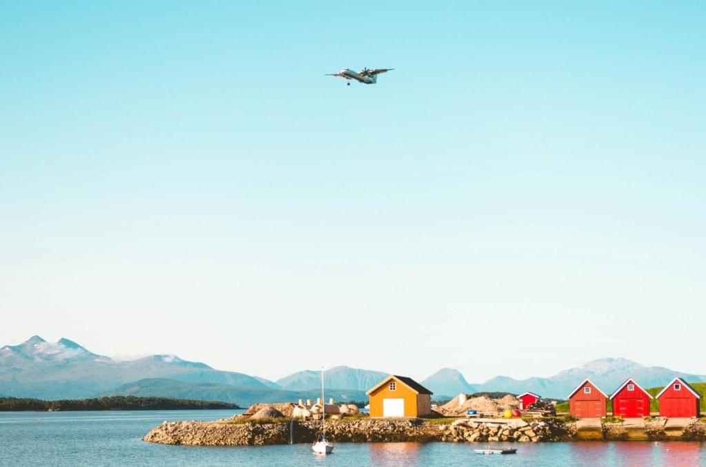 Fjord in Norwegen mit Holzhütte, blauer Himmel, Flugzeug