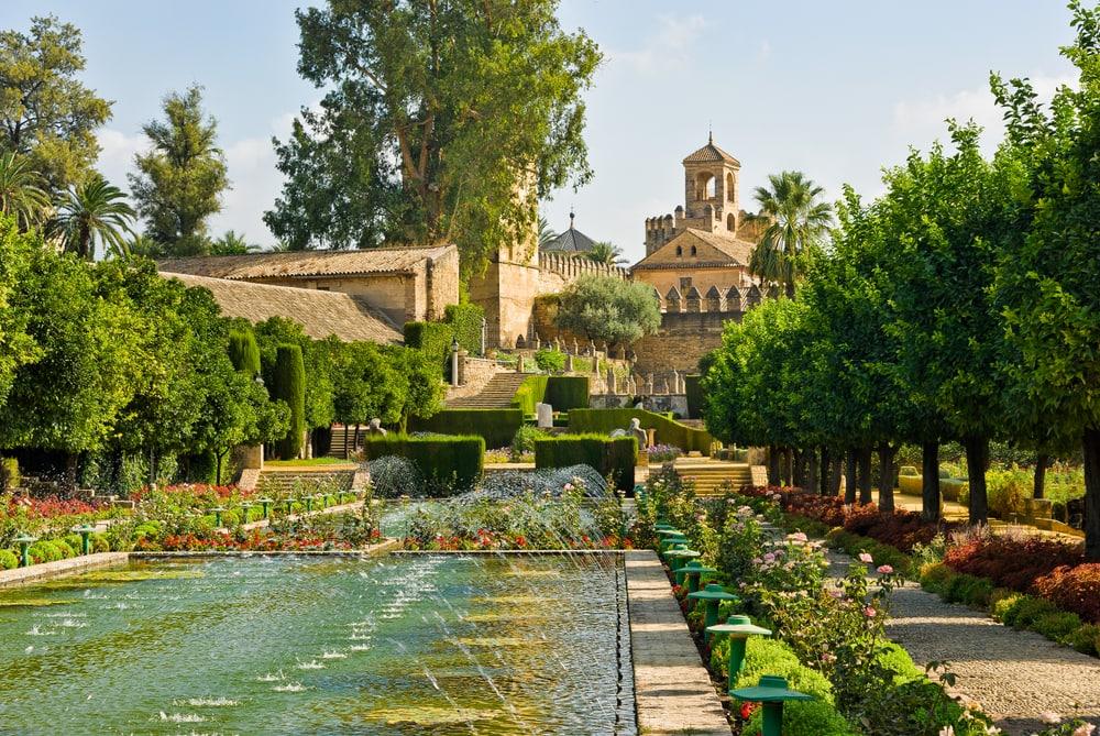 Grüner Garten mit altem Palast im Hintergrund und vielen Blumen und Brunnen.