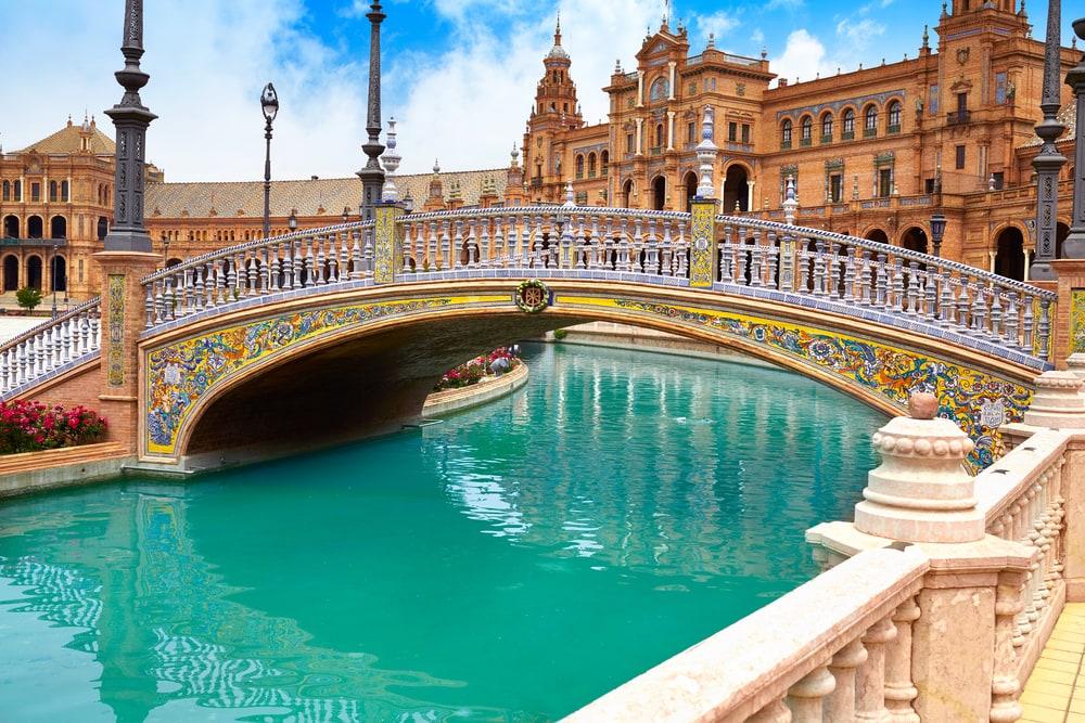 Großer Palast mit türkisem Kanal und glanzvoller Brücke.
