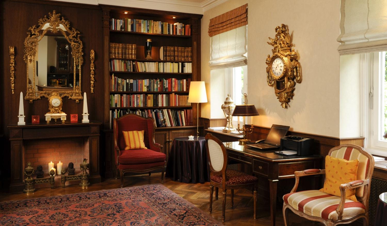 Gemütlicher Raum mit Bücherregal, Sesseln, orientalischem Teppich und altem Schreibtisch