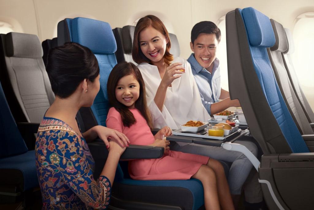 Singapore Girl kniet vor Familie in der Economy Class