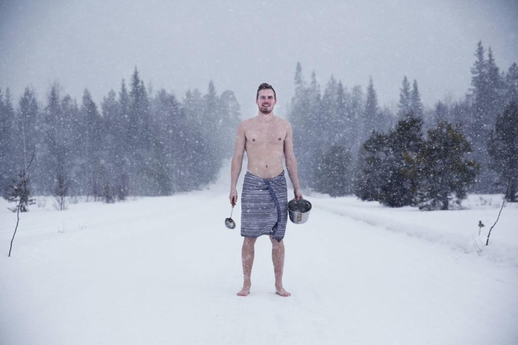 Mann steht halbnackt mit Sauna-Utensilien in finnischer Winterlandschaft