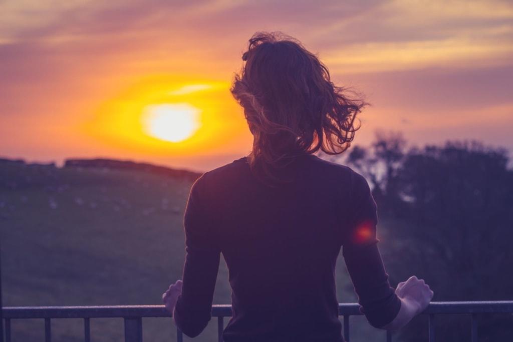 Frau auf Balkon stehend, blickt in Sonne