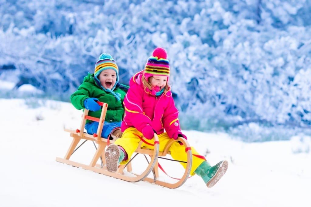 Kinder auf Schlitten im Winter