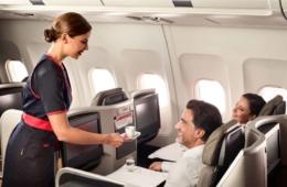 Flugbegleiterin der TAP bedient zwei Passagiere in der Business Class