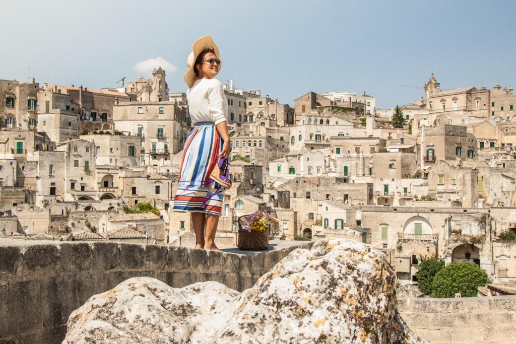 Frau mit Sonnenhut und Brille steht fotogen auf Mauer, im Hintergrund die Altstadt von Materna