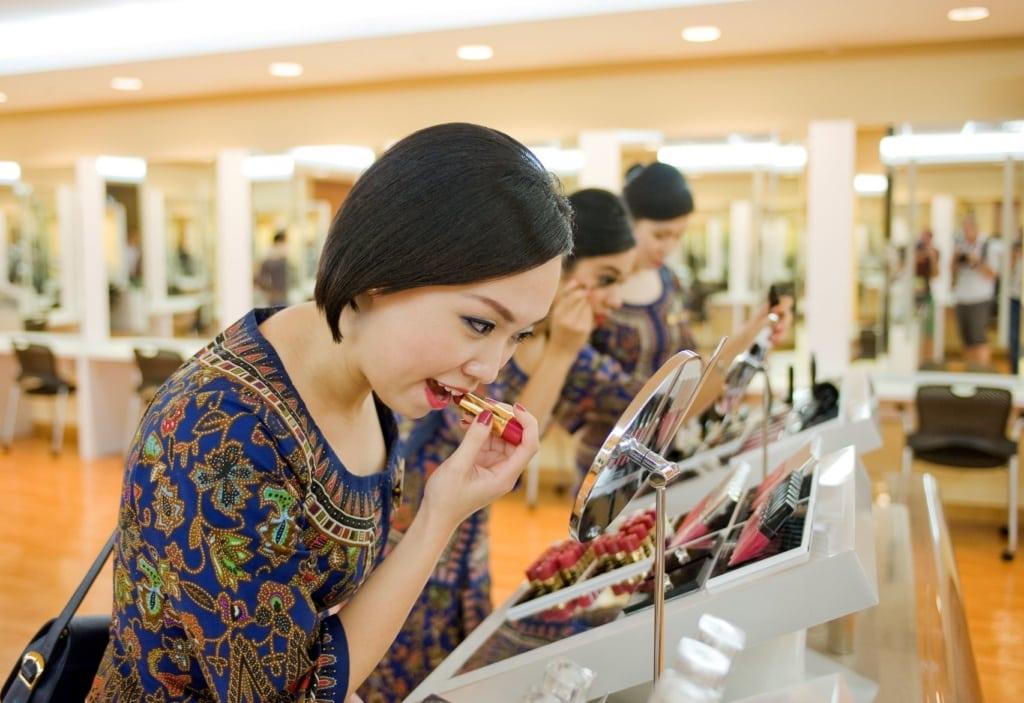 Singapore Girl mit Lippenstift vor Spiegel