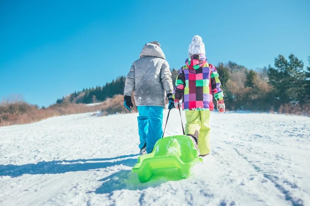 Zwei Kinder ziehen einen grünen Plastikschlitten den Berg hinauf